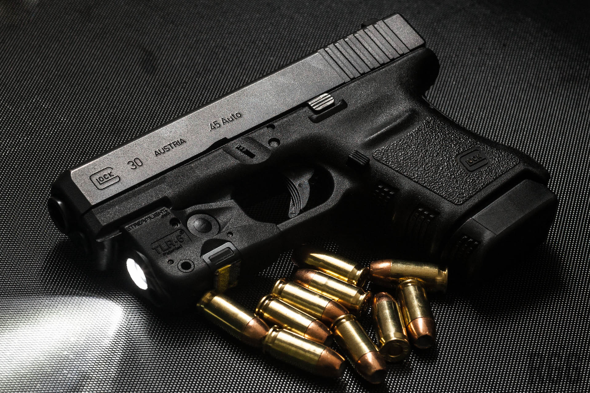 A GLOCK 30 45 ACP pistol with a Streamlight TLR-6 weapon mounted light.