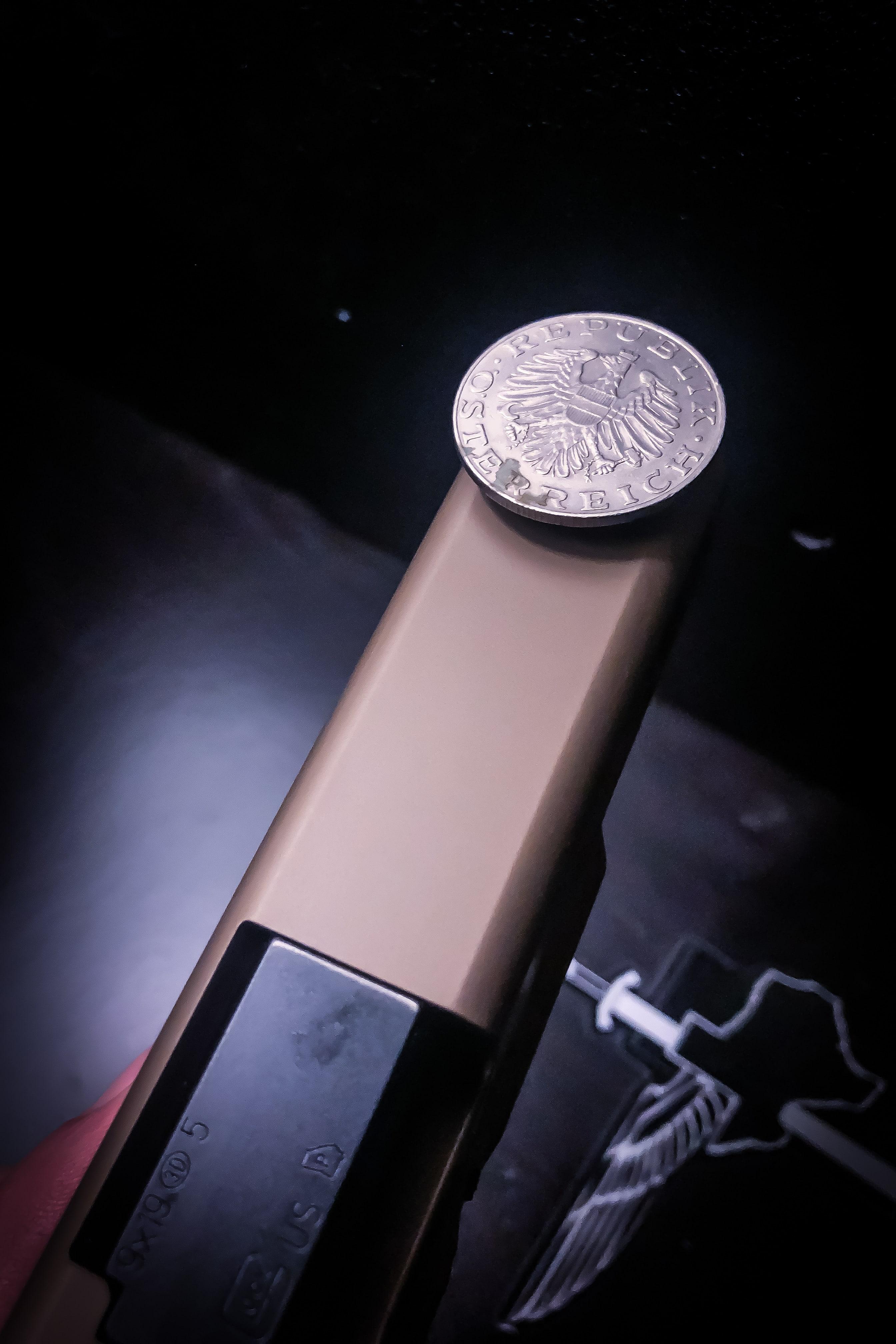A GLOCK 19x with an Austrian 10 Schilling coin balanced.