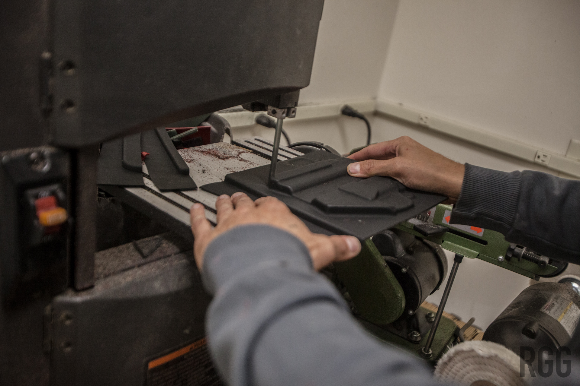 Orion uses a band saw to cut the excess Kydex from the unfinished holster...